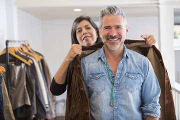 Woman helping man with fringe jacket in store