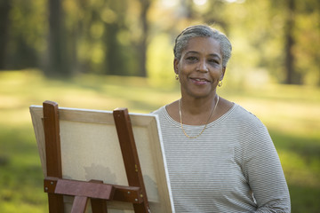 Portrait of Black woman painting on canvas in park