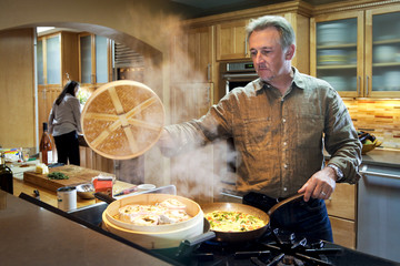 Caucasian man steaming food on stove in the kitchen