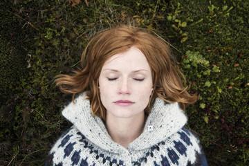 Portrait of woman lying on moss