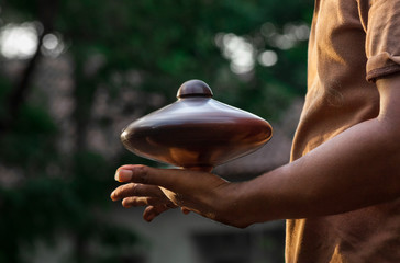 Gasing player holding spinning top in his hands