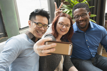 Business people posing for cell phone selfie in office