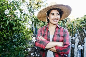 Smiling Mixed Race woman standing in garden