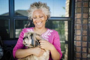 Black woman hugging dog near window