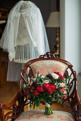 Wedding bouquet with red and white peonies stands on the chair before wedding dress