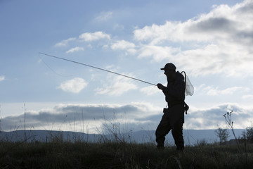 Silhouette of Caucasian man carrying fishing rod in field