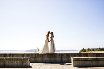 Caucasian brides kissing at waterfront