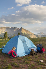 Young girl setting up camp tent along Colorado Trail near Trout Lake and?Kennebac?Pass in San Juan National Forest