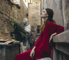 Caucasian woman wearing red dress sitting on bench in alley