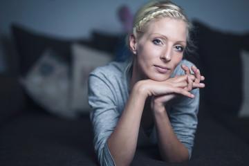 Blonde junge Frau liegt auf dem Sofa (frontal zur Kamera)