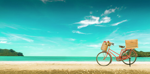 Red vintage bicycle on white sand beach over blue sea and clear blue sky background, spring or summer holiday vacation concept,vintage style.