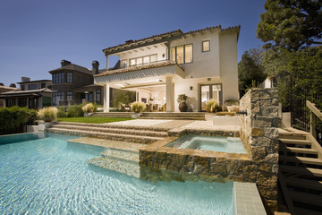 Swimming pool behind multiple story contemporary home