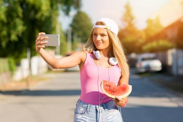 Millennial teenage girl with watermelon and headphones taking a selfie on smart phone