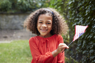 Portrait of smiling Mixed Race girl waving little American flag