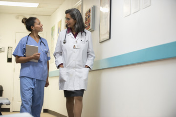 Mixed Race doctor talking with nurse carrying digital tablet