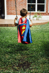Boy wearing superhero costume on swing