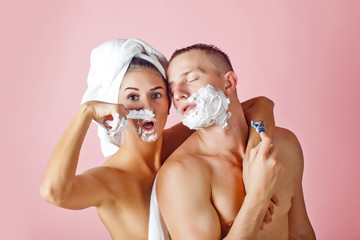 Man shaving and his girlfriend makeup. Beautiful young couple have fun in front of her bathroom.