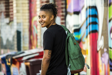 Portrait of smiling androgynous Mixed Race woman near on graffiti wall