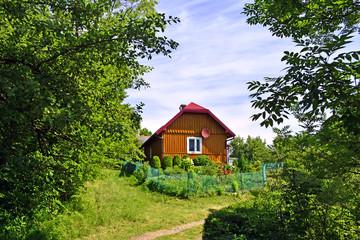 Fototapeta Brązowy, drewniany domek wśród zieleni obraz