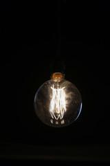 Oldstyle wolfram light bulb shining in the dark