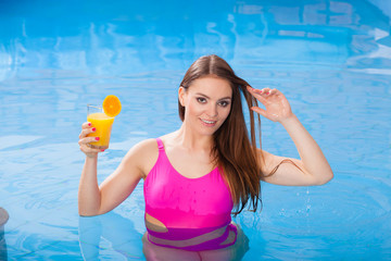 Girl with cocktail drink relaxing at swimming pool