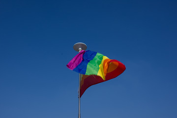 Rainbow flag waving on wind, blue sky background.