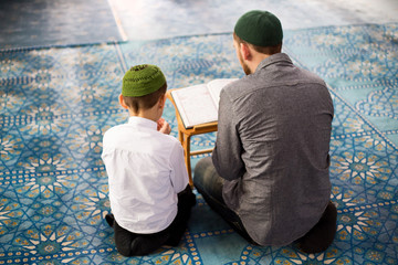 Father and sons pray in the mosque