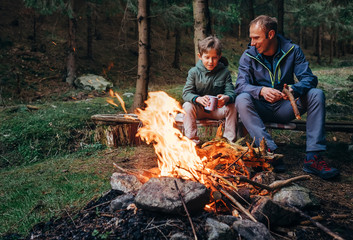 Father with son warm near campfire, drink tea and have conversation