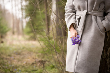 Closeup of woman's hands holding bunch of fresh wild snowdrops. spring flowers in girl's hands.