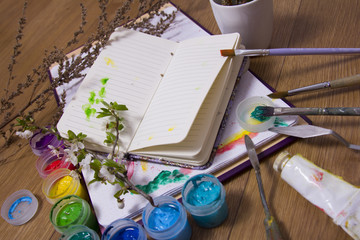 Creative artist workplace flat lay, mockup. top view on table with blank sketchbook, paintbrushes and dye palettes. Art, workshop, painting, drawing, craft, creativity concept