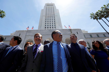 """Members of the Los Angeles City Council and their guests stand for a moment of unity during the """"Hands Around City Hall"""" event in recognition of the 25th anniversary of the start of the LA riots"""