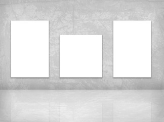 Mock up posters template. Three  blank canvas on the grey wall.