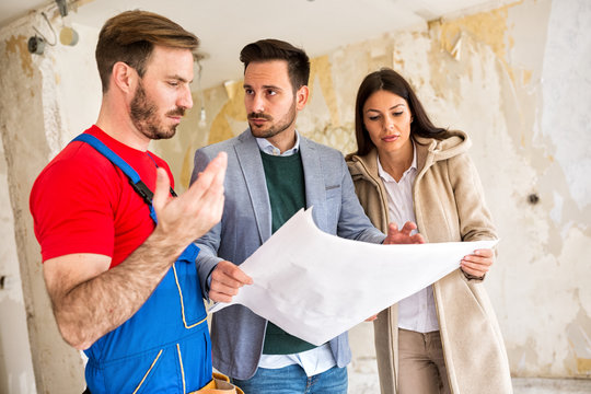 Builder handyman shows to young couple problem iin blueprints of their home