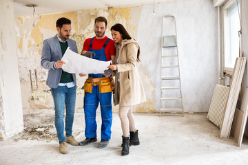 Beutiful young couple looking blueprints of their home with handyman