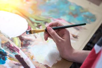 Asian man painting brush watercolors on paper. Wall mural