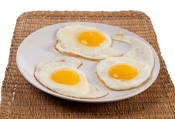 Three fried sunny side up eggs on white plate