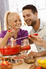 Loving couple having cheese fondue