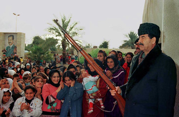 Iraqi President Saddam Hussein, wearing civilians clothes, holds a rifle during the celebration of t..