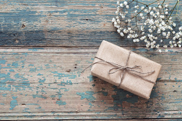 Rustic gift box with floweron the old grunge painted boards. Place for text.