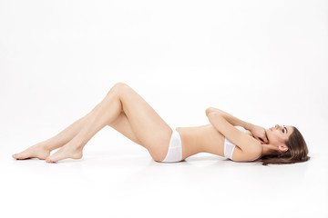 young beautiful brunette woman with long slender legs in white underwear  lies on  back on white background