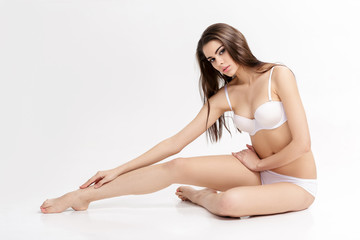 young beautiful brunette woman with long slender legs in white lunderwear sitting on floor on white background