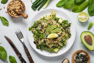 Fresh quinoa salad with spinach, avocado, seeds and Pine nuts. Top view. Vegan food.
