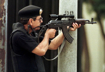 An elite special policeman takes aim through a high-powered scope at rebels after gunfire was heard ..