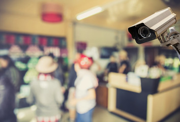 Image of CCTV security camera on blurred coffee shop background.