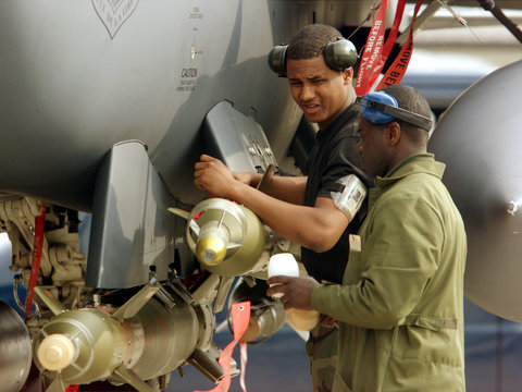 US SOLDIERS PREPARE LASER GUIDED BOMBS OF A F15 PLANE AT AVIANO AIRBASE.