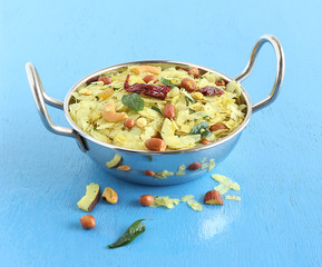 Indian traditional and popular snack poha chivda made from frying items like thin flattened rice, red chili, curry leaves, groundnuts, cashew nuts and almonds.