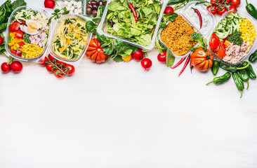 Healthy food concept. Variety of vegetables salad bowls in  plastic package on white wooden background, top view, border. Salad bar. Take away Diet lunch ideas