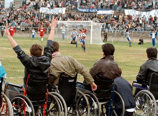 A disabled, former Bosnian government army soldier (L) celebrates a first goal of Zeljeznicar during..
