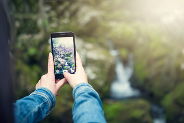 Young woman taking a photo with her phone of the falls in the middle of nature
