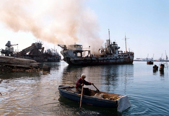 An  Albanian fisherman rows his boat towards burning harbour vessels in Durres seaport, March 25.  W..